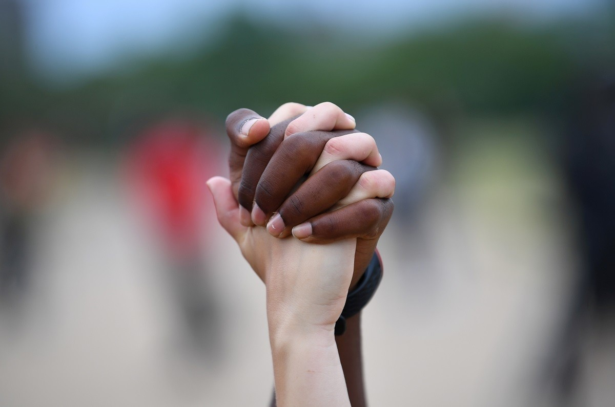 """A man and a woman hold hands aloft in Hyde Park during a """"Black Lives Matter"""" protest following the death of George Floyd who died in police custody in Minneapolis, London, Britain, June 3, 2020. REUTERS/Dylan Martinez     TPX IMAGES OF THE DAY - RC2O1H9T0C5L"""