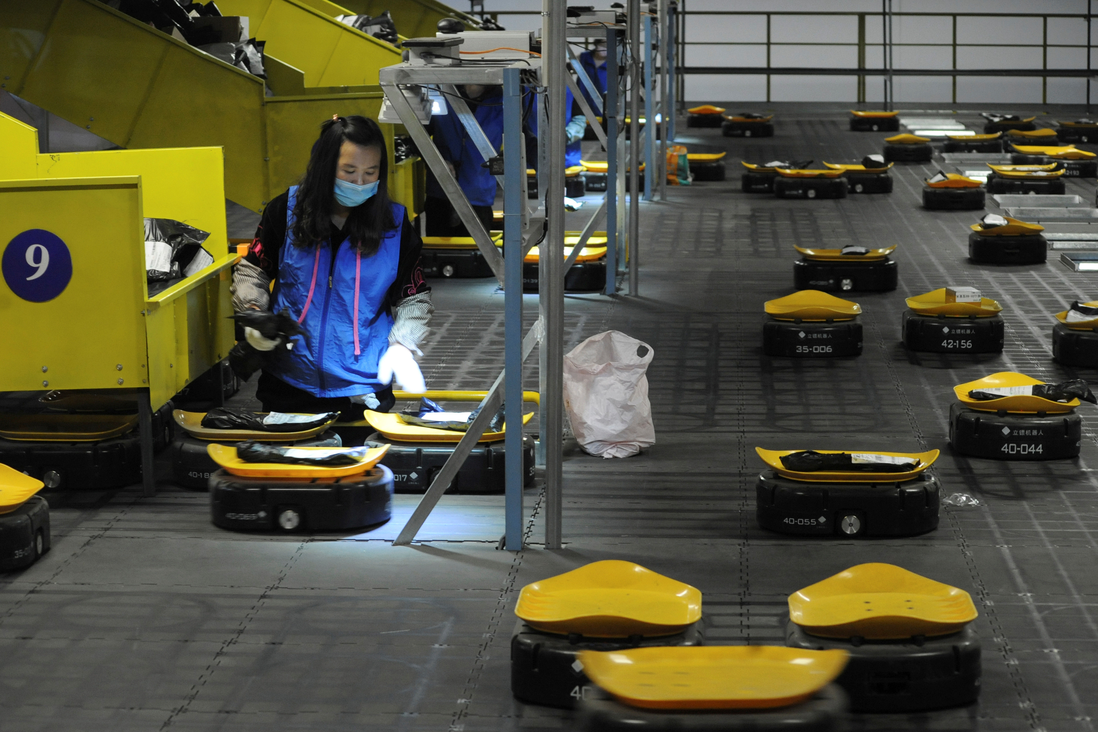 Employees sort parcels with automated guided vehicles (AGVs) at a logistic centre of a postal service a day ahead of the Singles' Day online shopping festival in Nanjing, Jiangsu province, China November 10, 2019. Picture taken November 10, 2019.