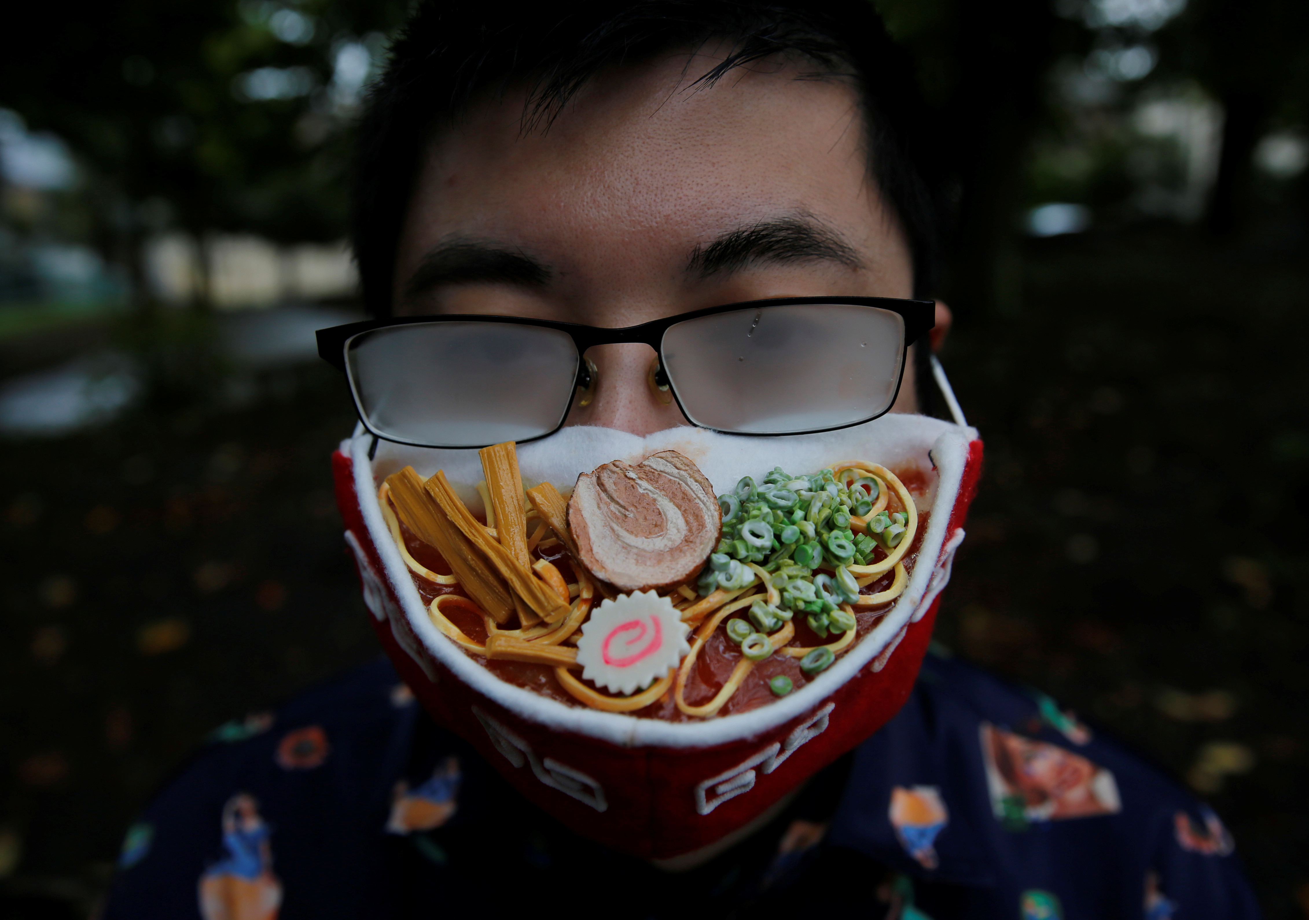 Japanese designer Takahiro Shibata's glasses fog up as he wears a protective mask that looks like a steaming bowl of ramen noodle soup while posing for a photo at a park, following the coronavirus disease (COVID-19) outbreak in Yokohama, Japan September 23, 2020. REUTERS/Kim Kyung-Hoon - RC2T4J91PDR9