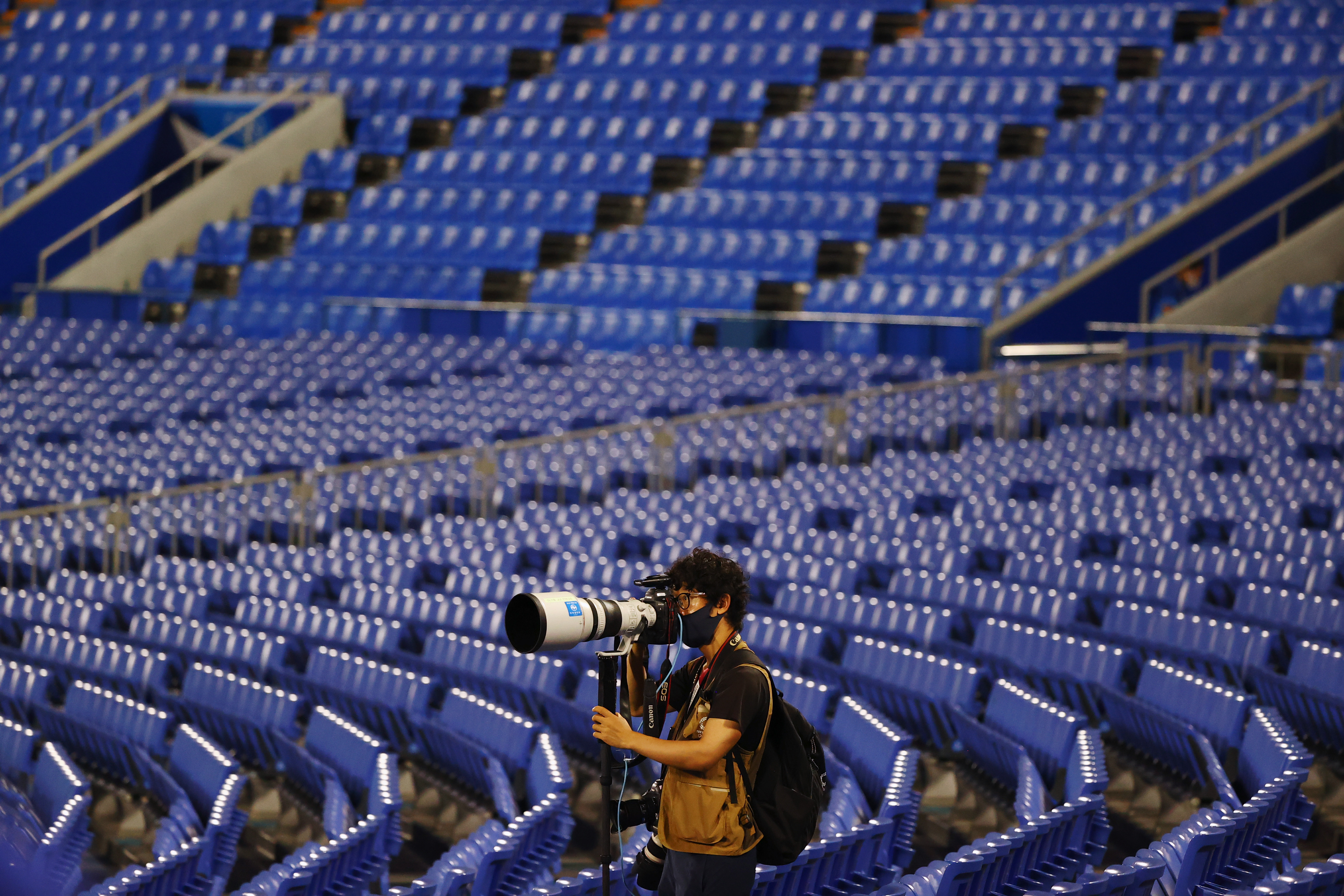 Tokyo 2020 Olympics - Softball - Women - Finals - Gold Medal Game - Japan v United States - Yokohama Baseball Stadium - Yokohama, Japan - July 27, 2021. A lone photographer works between empty seats in the stands as paying spectators are not allowed due to the coronavirus disease (COVID-19) pandemic. REUTERS/Jorge Silva - SP1EH7R0ZCXH7