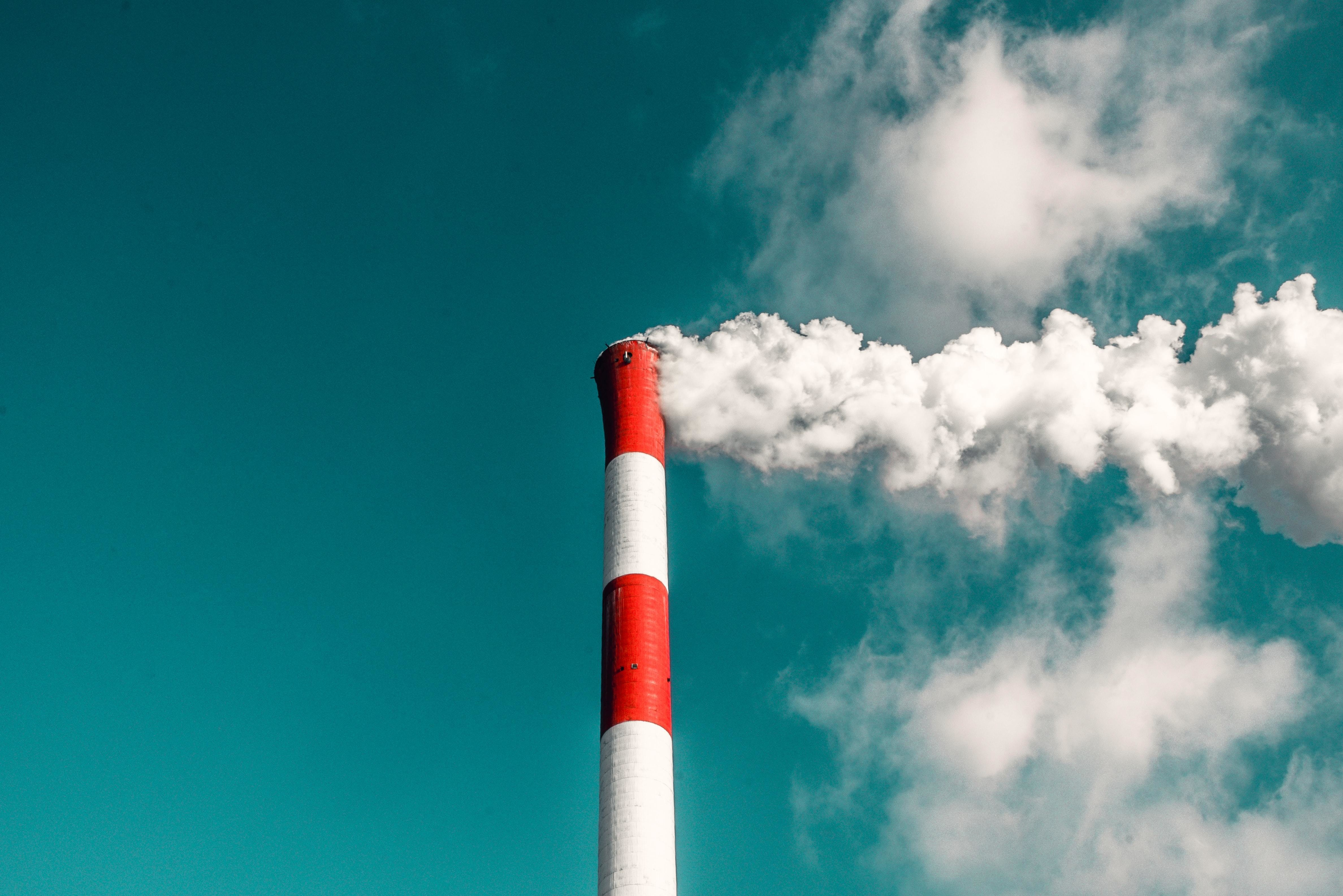 Industrial chimney billowing white smoke.