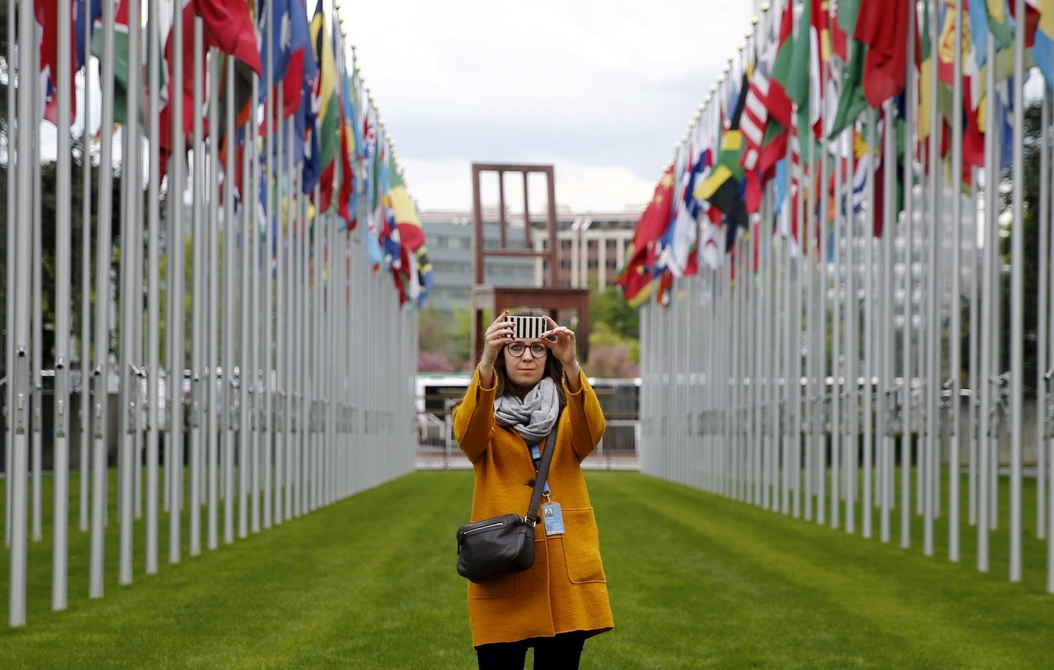 A staff takes a selfie in the flags alley at the European headquarters of the United Nations in Geneva, Switzerland, April 26, 2016.  REUTERS/Denis Balibouse - GF10000396206