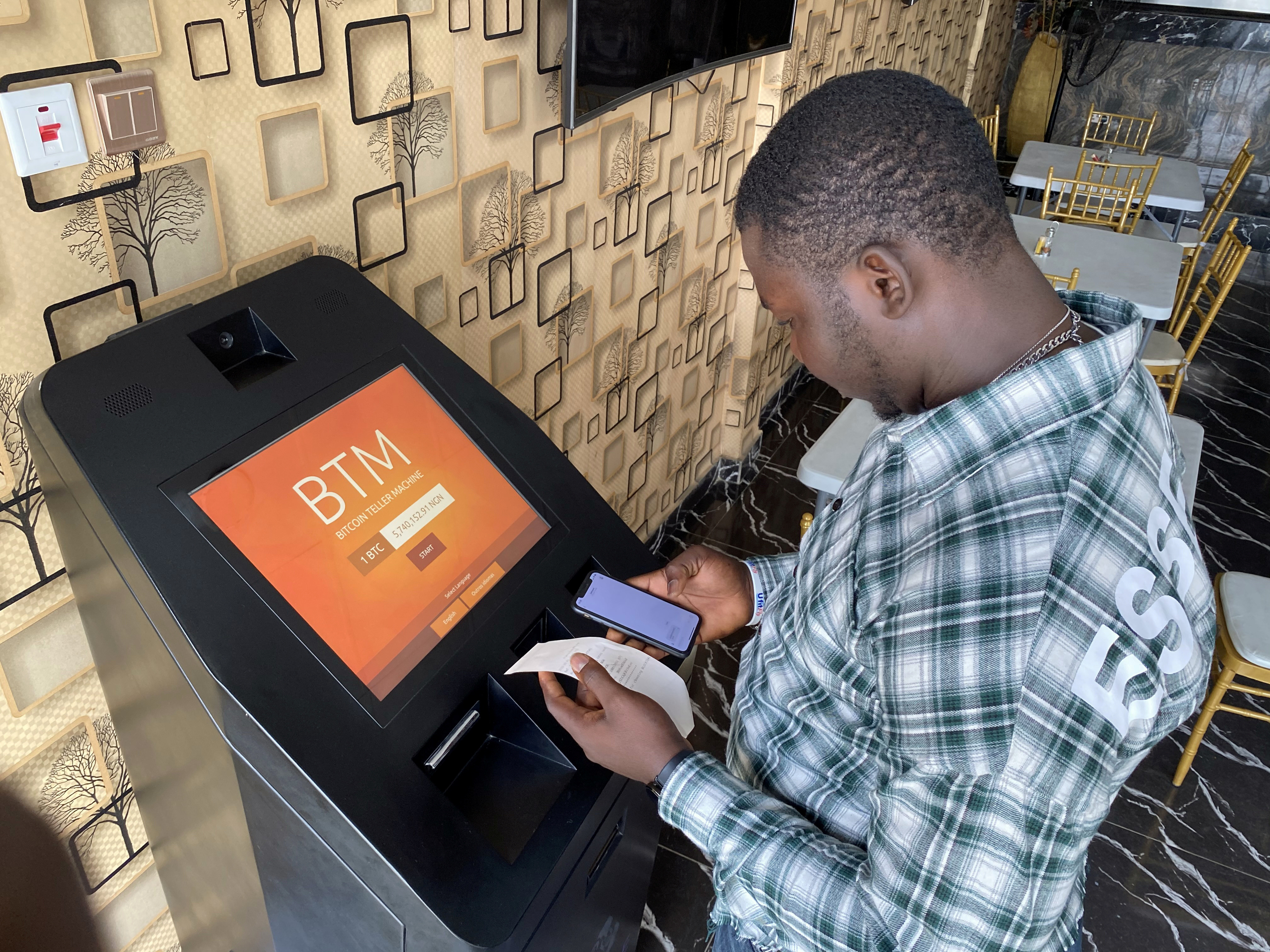 A bitcoin user checks the receipts after buying bitcoins with naira on Bitcoin Teller Machine in Lagos, Nigeria September 1, 2020. Picture taken September 1, 2020.