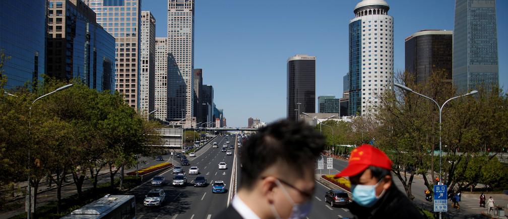 """Personas con máscaras protectoras cruzan un puente en el Distrito Central de Negocios en un """"día de cielo azul"""" en Beijing, mientras continúa la propagación de la nueva enfermedad coronavirus (COVID-19), en China el 22 de abril de 2020."""