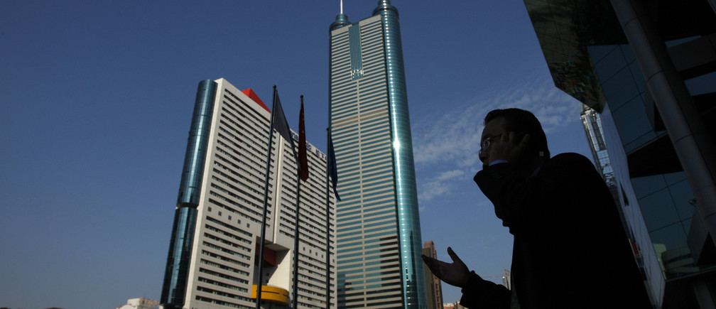A man talks on the mobile phone outside the Shenzhen Stocks Exchange opposite to the 384-metre (1,260 ft) tall skyscraper at Shun Hing Square in the southern Chinese city of Shenzhen in Guangdong province November 25, 2008.  REUTERS/Bobby Yip   (CHINA) - RTXAYBK