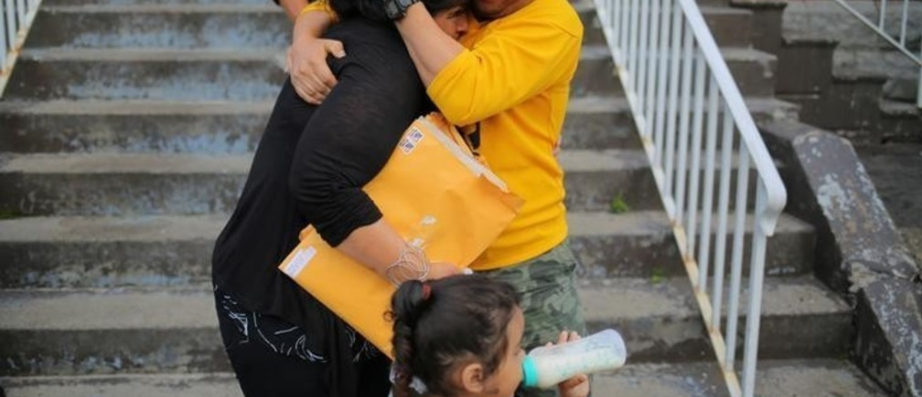 """A woman from El Salvador (L), requesting to be identified only as """"E"""" for her family's safety, is embraced by a family friend before leaving Vive La Casa shelter by taxi with her daughters to file a refugee claim at the Canadian border, in Buffalo, New York, U.S. July 5, 2017. Picture taken July 5, 2017. REUTERS/Chris Helgren"""