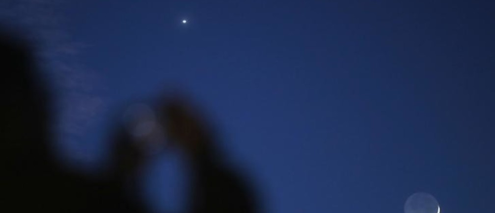 A man takes a picture of the crescent moon and planets Venus and Mars seen in the sky in central Bosnia February 20, 2015. People in Bosnia witnessed late Friday evening an astronomical event whereby Venus and Mars were accompanied by a crescent moon just after sunset. REUTERS/Dado Ruvic (BOSNIA AND HERZEGOVINA - Tags: ENVIRONMENT)