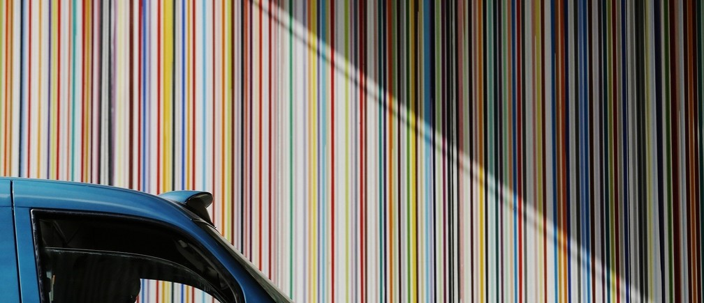 A taxi driver is silhouetted as she passes a poured paint public artwork by artist Ian Davenport in central London July 2, 2014.