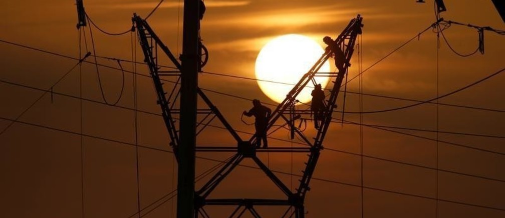 Technicians work on an electricity pylon as part of maintenance of high-tension electricity power lines, during sunset in Cantin, France, December 19, 2017. REUTERS/Pascal Rossignol - RC1D7721D540