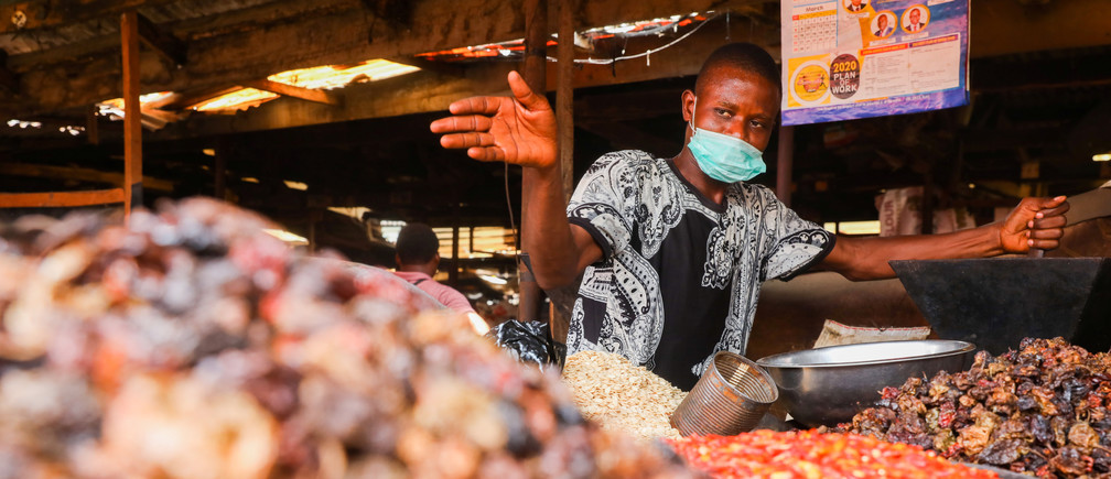 A trader gestures in his stall at a food market after Nigeria's President Muhammadu Buhari called for a lockdown starting tonight to limit the spread of coronavirus disease (COVID-19), in Lagos, Nigeria March 30, 2020.