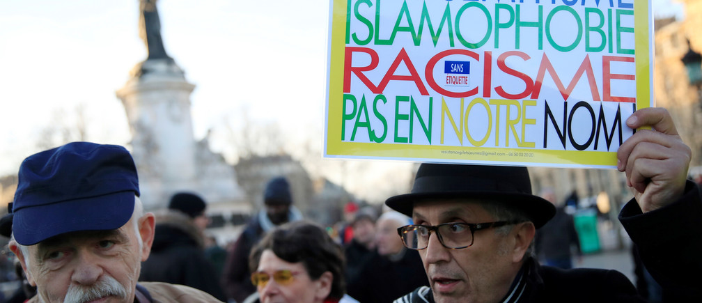 "People attend a national gathering to protest antisemitism and the rise of anti-Semitic attacks in the Place de la Republique in Paris, France, February 19, 2019. The writing on the sign reads: ""Antisemitism, islamophobia, racism - not in our name"".  REUTERS/Gonzalo Fuentes - RC1C0E9C21B0"