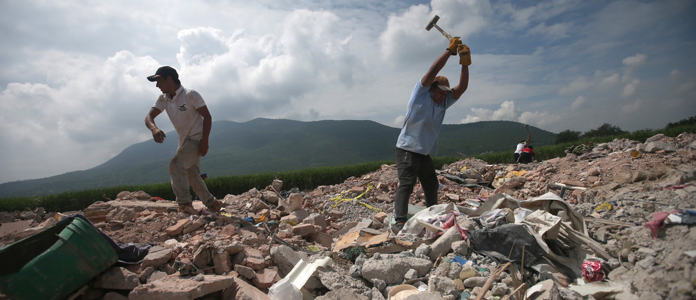 Men look for salvageable items at a site for the rubble of buildings damaged in the earthquake on the outskirts of Jojutla de Juarez, Mexico September 29, 2017.   REUTERS/Edgard Garrido - RC1CA2E0A270