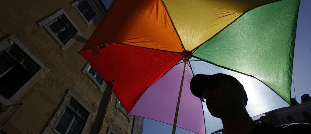 A man holds a umbrella with the colours of rainbow during the Gay Pride Parade in Lisbon June 28, 2008.