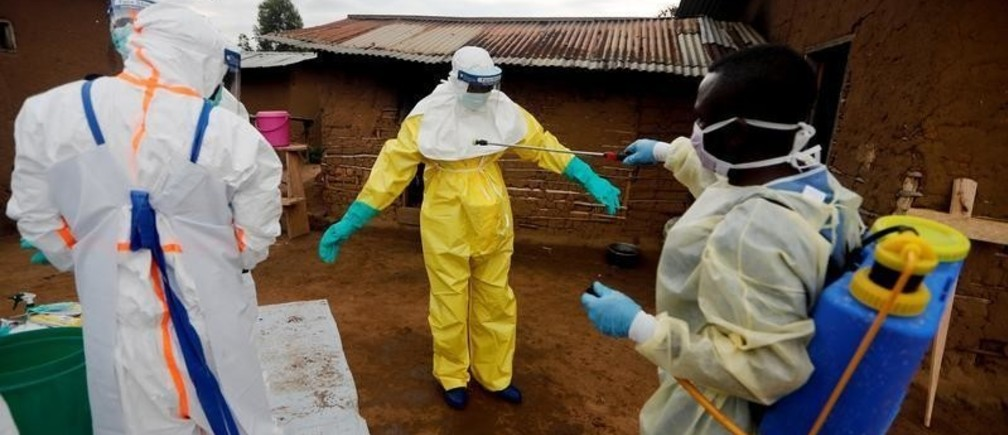 "Kavota Mugisha Robert, a healthcare worker, who volunteered in the Ebola response, decontaminates his colleague after he entered the house of 85-year-old woman, suspected of dying of Ebola, in the eastern Congolese town of Beni in the Democratic Republic of Congo, October 8, 2019. ""We came as fast as we got a call from his family, they were afraid to approach him."" I am aware of the risk of Ebola but I protect myself and I do not touch anything without my gloves. I help preserve my community from this deadly virus. "" Said Kavota. REUTERS/Zohra Bensemra   SEARCH ""EBOLA ZOHRA"" FOR THIS STORY. SEARCH ""WIDER IMAGE"" FOR ALL STORIES. - RC147174A210"