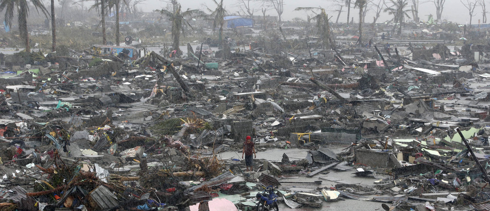 Survivors stand among debris and ruins of houses destroyed after Super Typhoon Haiyan battered Tacloban city in central Philippines November 10, 2013. Haiyan, one of the most powerful storms ever recorded killed at least 10,000 people in the central Philippines province of Leyte, a senior police official said on Sunday, with coastal towns and the regional capital devastated by huge waves. Super typhoon Haiyan destroyed about 70 to 80 percent of the area in its path as it tore through the province on Friday, said chief superintendent Elmer Soria, a regional police director.   REUTERS/Erik De Castro (PHILIPPINES - Tags: DISASTER ENVIRONMENT TPX IMAGES OF THE DAY) - GM1E9BA137I01