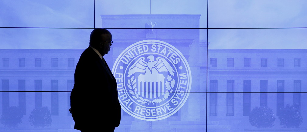 A security guard walks in front of an image of the Federal Reserve before the arrival of U.S. Federal Reserve Chair Janet Yellen to give a news conference following the two-day Federal Open Market Committee (FOMC) policy meeting in Washington, March 16, 2016.