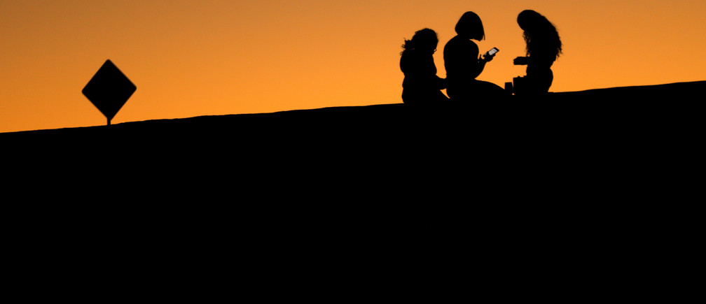 Young girls look at their phones as they sit on a hillside after sun set in El Paso, Texas, U.S., June 20, 2018.        REUTERS/Mike Blake - RC182A561FE0