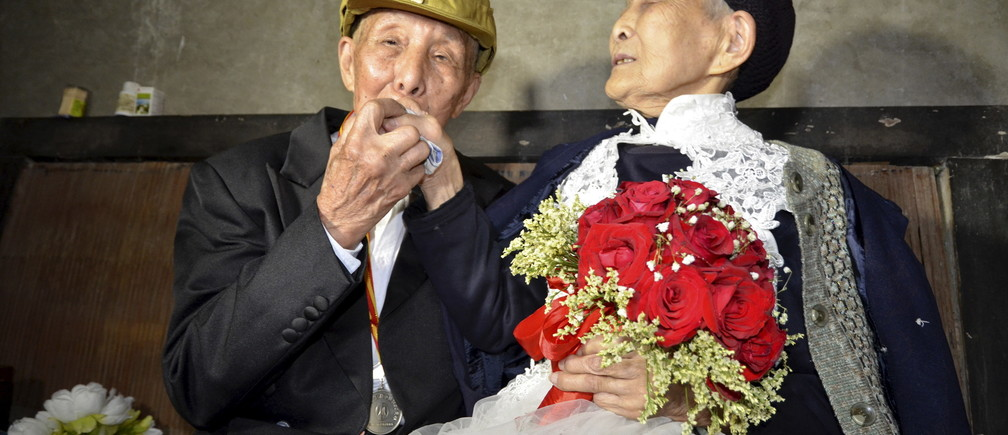Yan Zhengming (L), 94, kisses the hand of his wife Zhou Suqing, 90, during their wedding ceremony at their home, on the 70th anniversary of their marriage, in Quxian county of Dazhou, Sichuan province, China, May 15, 2015. The wedding, organized by local charity groups, was a long-time wish of veteran of the World War Two Yan, who married Zhou 70 years ago, but could not afford to have a wedding ceremony, local media reported