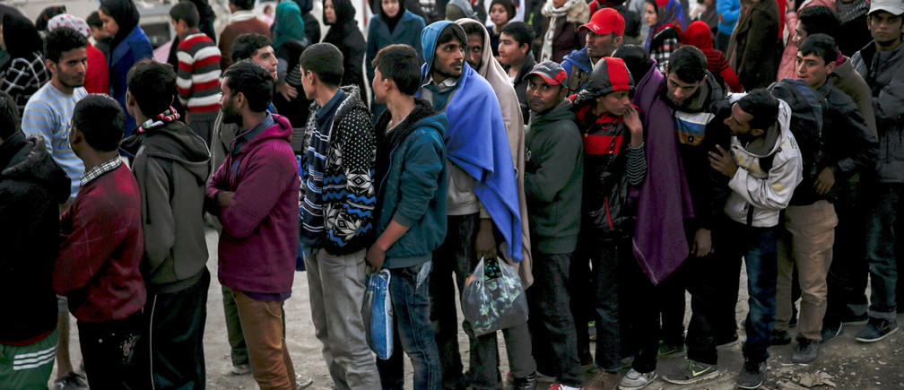 Refugees and migrants line up for a food distribution at the Moria refugee camp on the Greek island of Lesbos