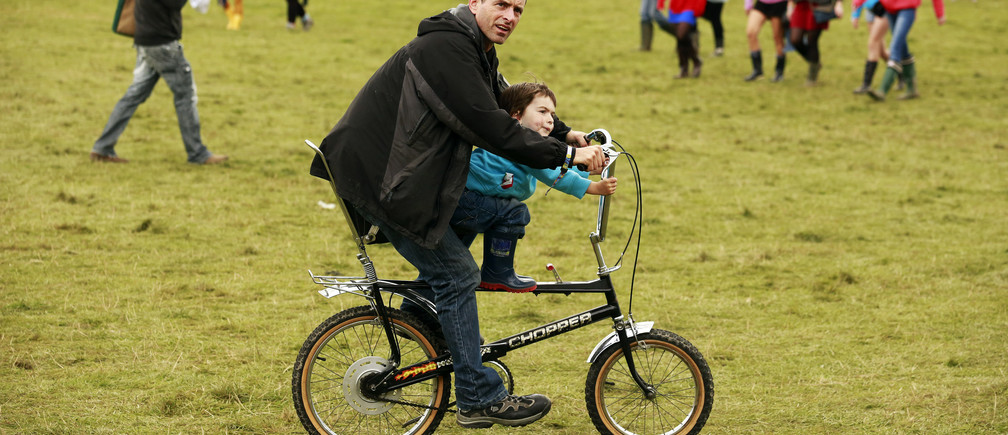 A man cycles with his son near the Little Big tent on the second day of Electric Picnic music festival at Stradbally Hall in County Laois August 30, 2014. REUTERS/Cathal McNaughton (IRELAND - Tags: ENTERTAINMENT SOCIETY) - GM1EA8U1QR401