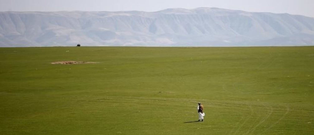 A man walks in a desert during an election campaign in Kunduz province, northern Afghanistan March 19, 2014. The Afghan presidential elections will be held on April 5.  REUTERS/Ahmad Masood (AFGHANISTAN - Tags: POLITICS ELECTIONS)