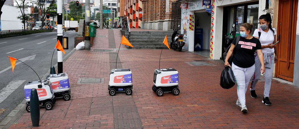 People wearing face masks watch delivery robots from the Colombian company Rappi traveling down a street, amid the coronavirus disease (COVID-19) outbreak in Medellin, Colombia April 17, 2020. REUTERS/David Estrada - RC2L6G94JJE5