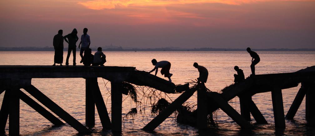 Boys cross a broken bridge across the Yangon river December 27, 2010.