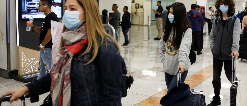 Les gens portent des masques de protection à l'aéroport international Benito Juarez après que le gouvernement mexicain ait déclaré vendredi avoir détecté les premiers cas d'infection par coronavirus du pays, à Mexico, Mexique, le 28 février 2020.