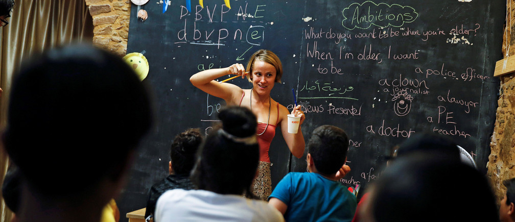 "British volunteer primary school teacher Helen Brannigan holds a pen and a cup as she conducts an English class to refugee children at the volunteer-run ""Refugee Education Chios"" school on the island of Chios, Greece September 6, 2016."
