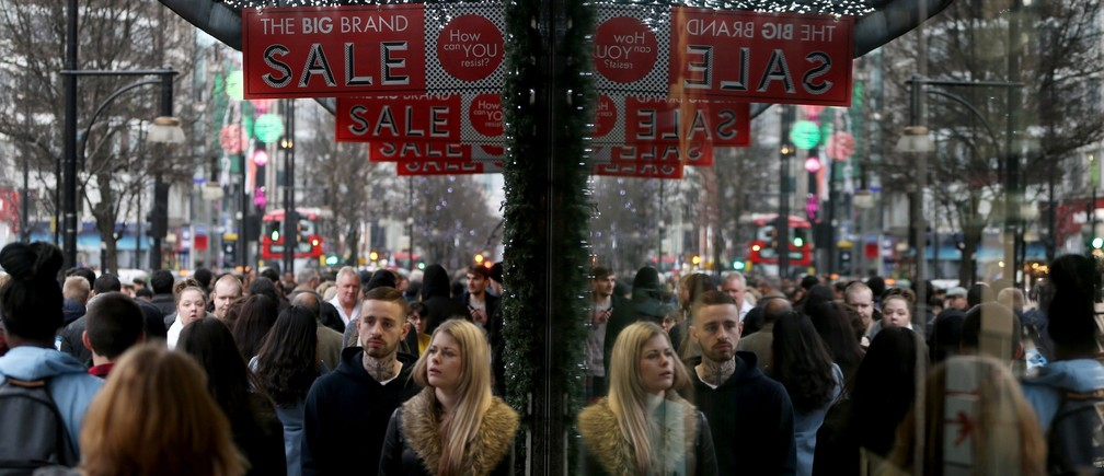Shoppers are reflected in a store window as they pass sales advertisements on Oxford Street in London, Britain December 26, 2015.