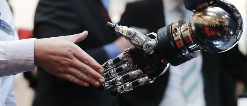 A woman reaches out to shake hands with a robotic hand at the booth of Schunk at the world's largest industrial technology fair, the Hannover Messe, in Hanover April 13, 2015