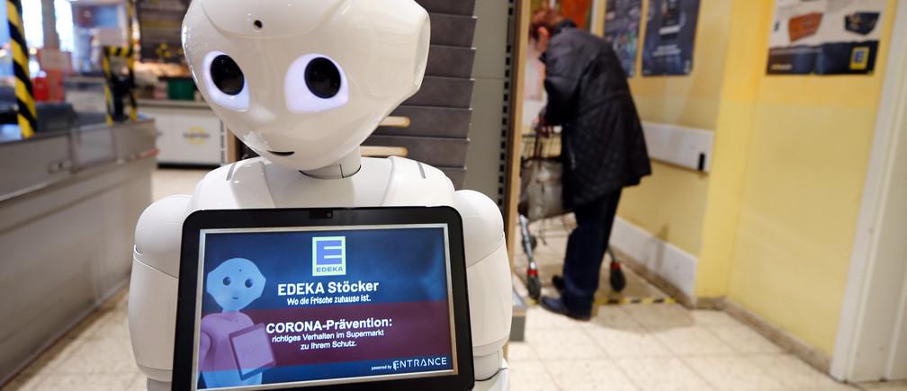 El robot humanoide Prepper está de pie en la caja de la tienda de comestibles Edeka para explicar las medidas de protección y promover la solidaridad entre ellos, mientras la propagación de la enfermedad coronavirus (COVID-19) continúa, en Lindlar, Alemania