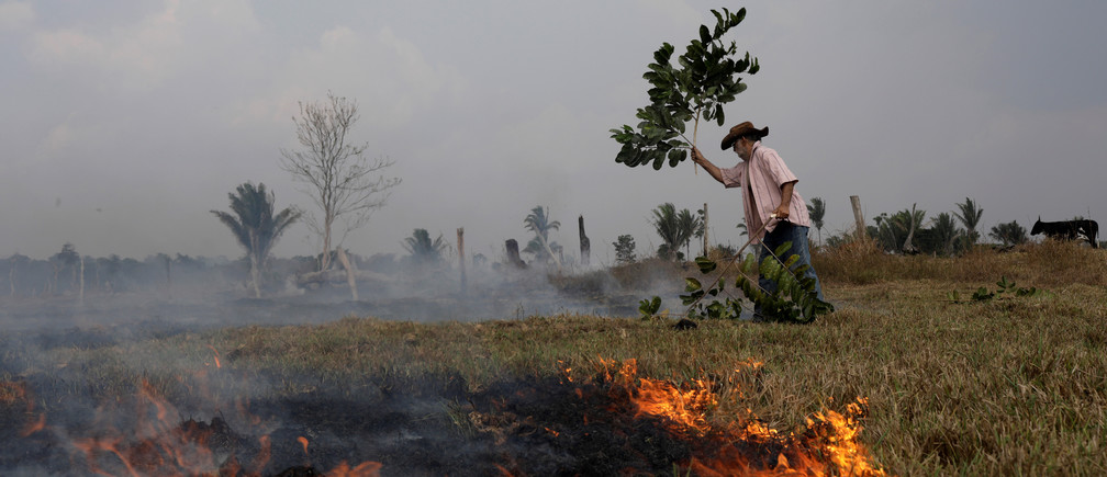 Avaci, 77, who is an employee of a farm, fights a fire on a field after it was hit by a fire burning a tract of the Amazon forest as it is cleared by farmers, in Rio Pardo, Rondonia, Brazil September 16, 2019. REUTERS/Ricardo Moraes - RC1FCAB375D0
