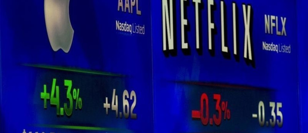 A reporter points at ticker symbols for Apple Inc. and Netflix displayed on a screen at the Nasdaq Market site in New York September 2, 2015. REUTERS/Brendan McDermid  - GF10000190713