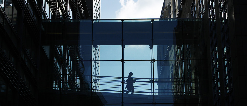 A woman crosses a walkway between Goldman Sachs offices in central London October 15, 2009.  Goldman Sachs posted better-than-expected quarterly earnings and stayed on track to hand out more than $20 billion in year-end bonuses.    REUTERS/Luke MacGregor   (BRITAIN BUSINESS) - LM1E5AF19XJ01