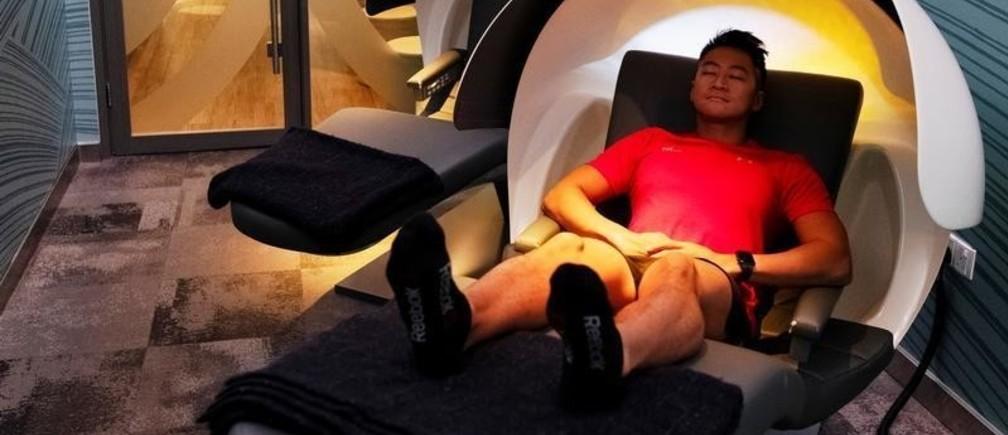 A Virgin Active employee demonstrates the use of a MetroNaps EnergyPod for power naps at their fitness club in central Singapore, March 5, 2019. Picture taken March 5, 2019. REUTERS/Loriene Perera - RC199C15C690
