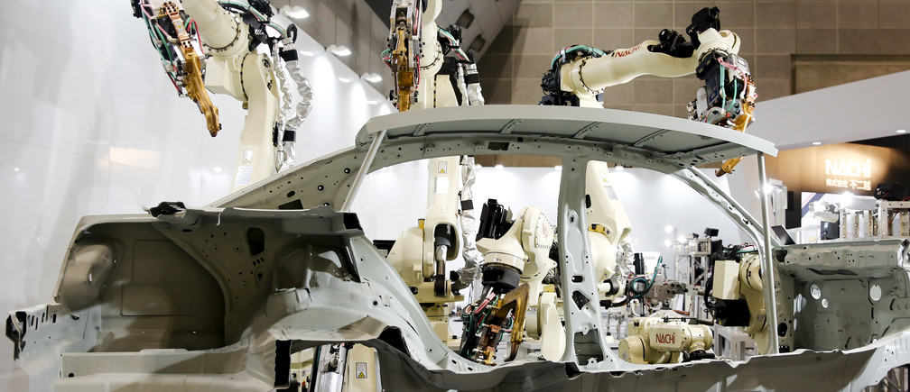 Robot arms by Nachi Robotic Systems work on the body of a car at the International Robot Exhibition in Tokyo, Japan December 2, 2015.