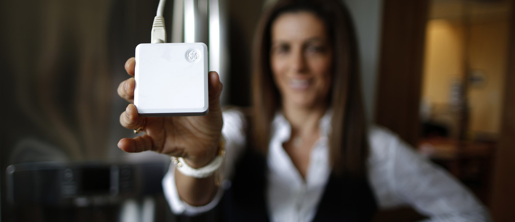 Computer science professor Christa Lopes holds an appliance communication module attached to the refrigerator in her home in Irvine, California January 26, 2015. Lopes said the Irvine Smart Grid Demonstration, a $79 million project funded half by federal stimulus money and half by Edison and partners like UC Irvine, cut her electric bill to zero in the summer. The $12 billion utility's research team Southern California Edison is testing everything from charging electronic vehicles via cell phone to devices that smooth out the power created by rooftop solar panels. Those are some of the roughly 60 projects in the works at Edison's Advanced Technology division. It has a small $19 million annual budget, but its influence far exceeds that. Picture taken January 26, 2015.