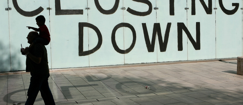 Shoppers walk past a closing down sign in a shop window in Cardiff, Wales, September 9 , 2009. REUTERS/Phil Noble (BRITAIN BUSINESS EMPLOYMENT) - LM1E5991FVZ01