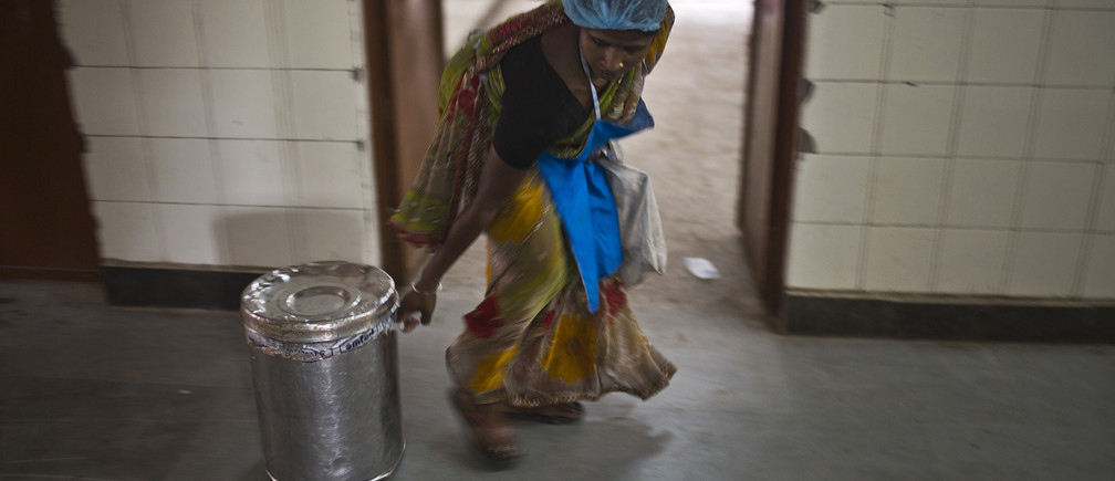 A worker pulls a container carrying a free mid-day meal, distributed by a government-run primary school, for school children in New Delhi July 19, 2013. Health officials in the eastern Indian state of Bihar were due on Friday to release autopsy results for many of the 23 school children who died on Tuesday after vomiting and convulsing with agonizing stomach cramps. The children fell ill within minutes after eating a lunch provided by their school in the village of Gandaman. The free meals are part of a national scheme aimed at tackling malnutrition and encouraging children to attend school. REUTERS/Ahmad Masood (INDIA - Tags: DISASTER HEALTH FOOD EDUCATION) - GM1E97J1OVL01
