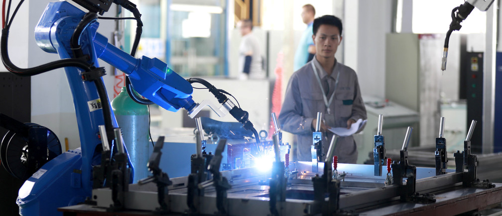 A worker monitors a robotic arm working inside a factory in Huaian, Jiangsu province, China May 15, 2018. Picture taken May 15, 2018.  REUTERS/Stringer  ATTENTION EDITORS - THIS IMAGE WAS PROVIDED BY A THIRD PARTY. CHINA OUT. - RC1360033A90