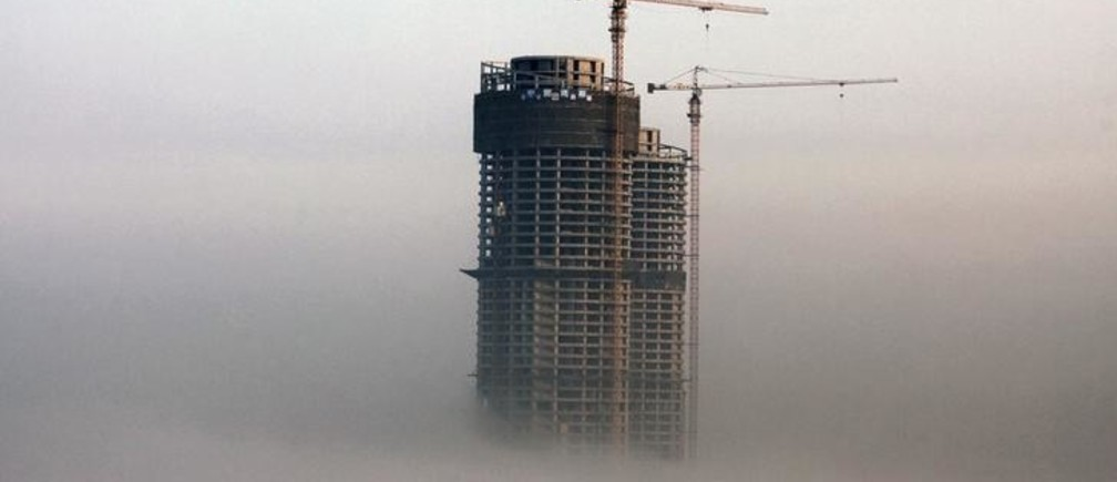 A building under construction is seen in fog in Rizhao, Shandong province, February 26, 2014. China's property market is likely to see at most a moderate correction in prices in some small cities this year, according to a Reuters straw poll of 13 industry watchers this week, with the chance of a sharp fall in prices nationwide very slim. Picture taken February 26, 2014. REUTERS/Stringer (CHINA - Tags: BUSINESS CONSTRUCTION REAL ESTATE ENVIRONMENT) CHINA OUT. NO COMMERCIAL OR EDITORIAL SALES IN CHINA