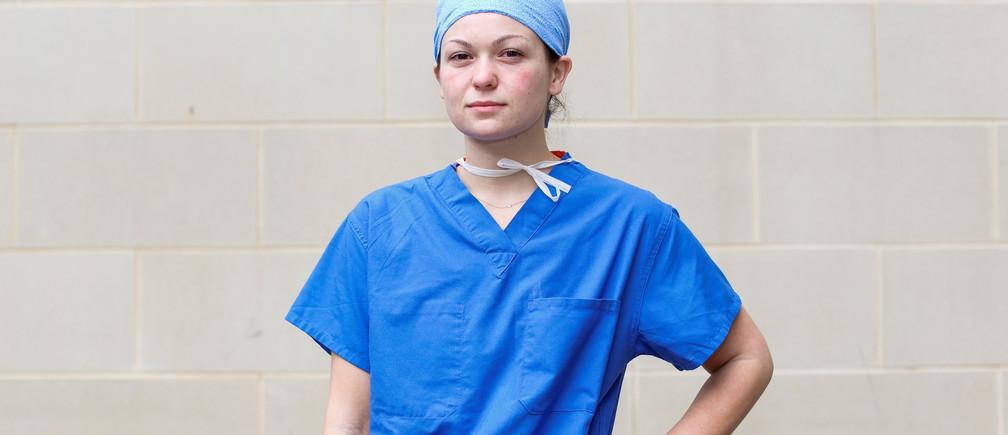 Julia Trainor, de 23 años, enfermera titulada que atiende a pacientes con COVID-19 en una unidad de cuidados intensivos quirúrgicos (UCI), posa para una fotografía después de un turno de 14 horas, fuera del hospital donde trabaja, durante el brote de la enfermedad coronavirus (COVID-19), Maryland, EE.UU., 8 de abril de 2020.