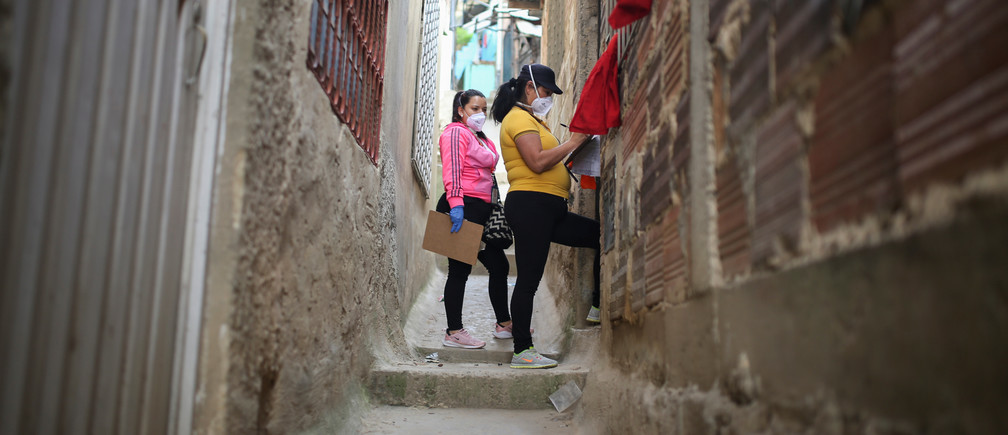 Mayoral employees walk through a poor neighborhood during a day of food aid delivery, amid the outbreak of the coronavirus disease (COVID-19) in Bogota, Colombia April 21, 2020.