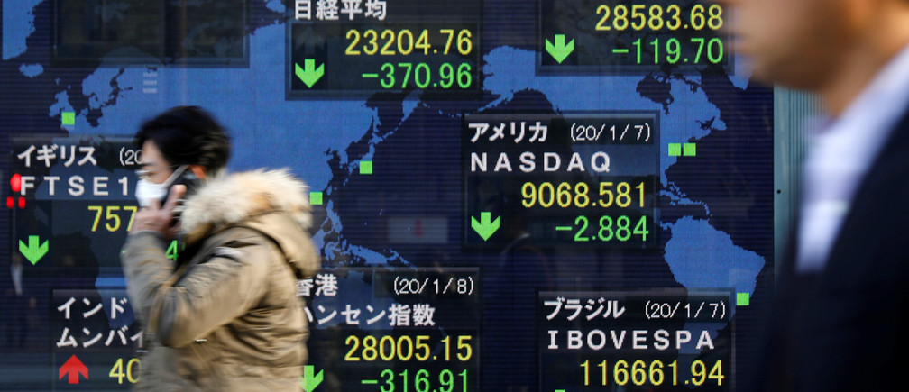 People walk past an electronic display showing world markets indices outside a brokerage in Tokyo, Japan, January 8, 2020.