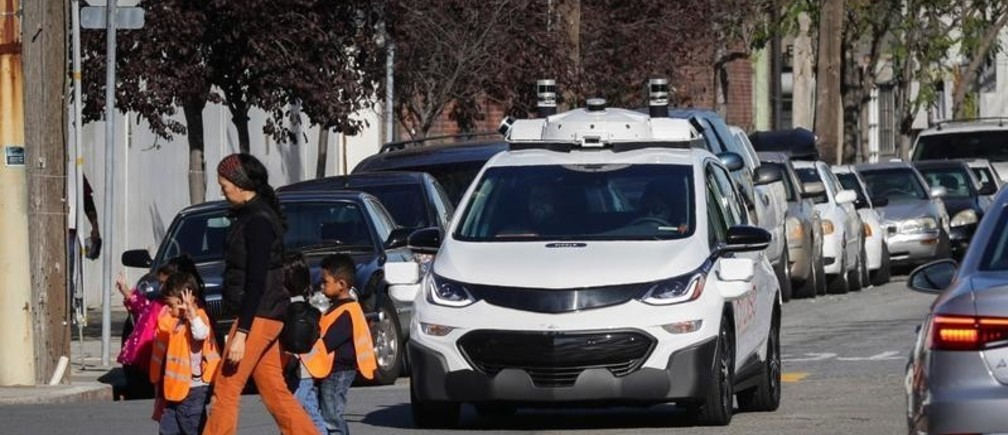 Children pass by a self-driving Chevy Bolt EV car during a media event by Cruise, GM's autonomous car unit,  in San Francisco, California, U.S. November 28, 2017. REUTERS/Elijah Nouvelage - RC17AC9914F0