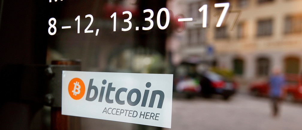 """A sticker that reads """"Bitcoin accepted here"""" is displayed at the entrance of the Stadthaus town hall in Zug, Switzerland, August 30, 2016. Picture taken August 30, 2016.  REUTERS/Arnd Wiegmann  - RTX2OLTJ"""