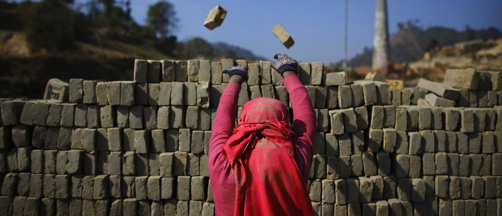 A girl throws away broken bricks while unloading bricks at a brick factory in Lalitpur December 19, 2012. REUTERS/Navesh Chitrakar (NEPAL - Tags: BUSINESS CONSTRUCTION SOCIETY TPX IMAGES OF THE DAY) - GM1E8CJ1HTR01