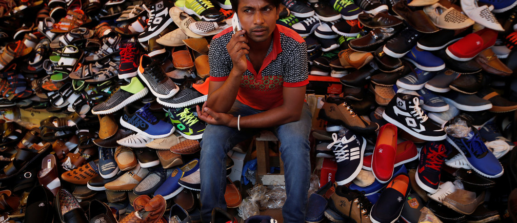 A vendor speaks on his mobile phone as he waits for customers at his shoe shop in the old quarters of Delhi, India June 12, 2017. REUTERS/Adnan Abidi - RC12FAE9F360