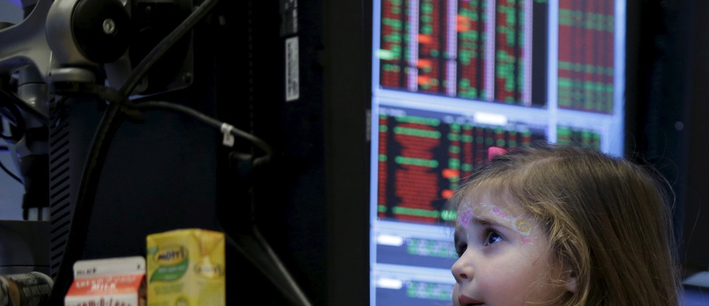 Victoria Parrinello sits inside her father's booth on the floor of the New York Stock Exchange, November 27, 2015. Traders traditionally bring their kids to work for half day of trading on the Friday after Thanksgiving holiday.